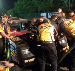 Members of the UNOH Motorsports team work on the No. 2 stock car moments before the feature race Friday at Limaland