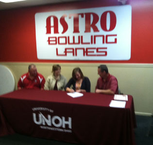 Casey Feltz signs her letter of intent with her parents and UNOH coach Todd Book looking on